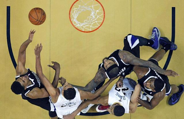 Sacramento Kings small forward Rudy Gay, left, shoots against New Orleans Pelicans center Alexis Ajinca, second left, and power forward Anthony Davis (23), while Kings center DeMarcus Cousins and power forward Jason Thompson, right, box them out, in the second half of an NBA basketball game in New Orleans, Tuesday, Jan. 21, 2014. The Kings won 114-97. (AP Photo/Gerald Herbert)