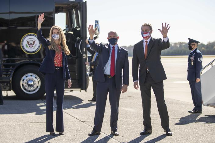 Vice President Mike Pence, center, Senator Kelly Loeffler, left, and Senator David Perdue, right, wave at individuals at Dobbins Air Reserve Base in Marietta, Ga., Friday, Nov. 20, 2020. Pence arrived on Friday to support Loeffler and Perdue, who are both facing a run-off election in January. (Alyssa Pointer /Atlanta Journal-Constitution via AP)