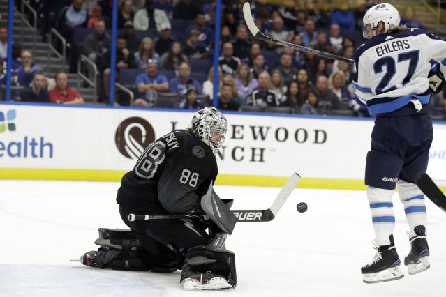 Winnipeg Jets left wing Nikolaj Ehlers (27) tries to deflect a shot by Tampa Bay Lightning goaltender Andrei Vasilevskiy (88) during the first period of an NHL hockey game Saturday, Nov. 16, 2019, in Tampa, Fla. (AP Photo/Chris O'Meara)