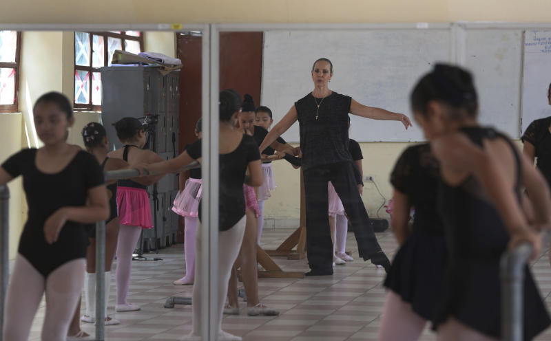 In this April 2, 2019 photo, Maria del Carmen Silva, a former professional dancer, instructs a group of young dancers in a studio at a public school in the Chorrillos neighborhood, a poor part of Lima, Peru. Silva is convinced that the discipline required in ballet will teach life lessons to her low-income students for whom hardship has come at an early age. (AP Photo/Martin Mejia)