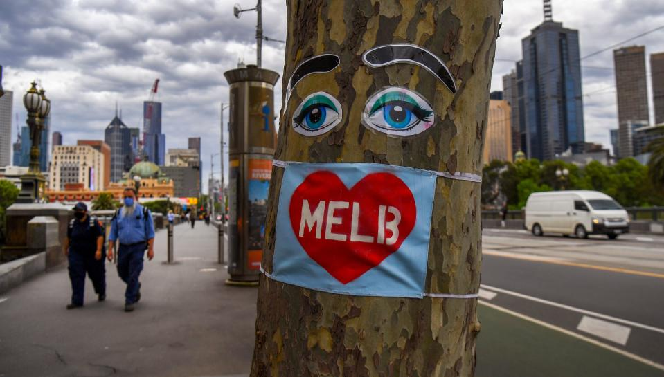 People walk past a tree decorated with eyes and a face mask in Melbourne's central business district on October 15, 2020, as Australia's unemployment rate ticks up to 6.9 percent. (Photo by William WEST / AFP) (Photo by WILLIAM WEST/AFP via Getty Images)