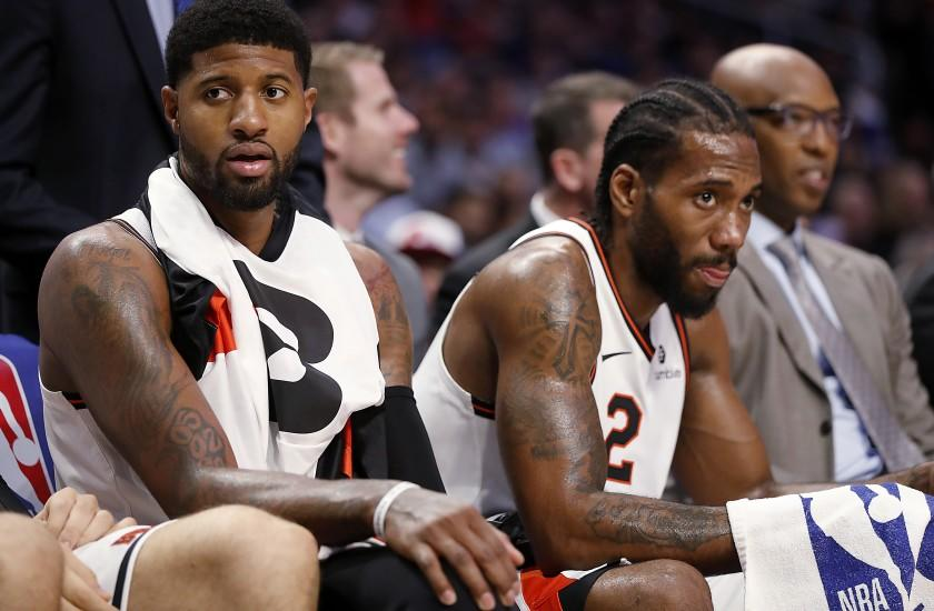 LOS ANGELES, CALIF. - DEC. 3, 2019. Clippers stars Paul George, left, and Kawhi Leonard rest on the bench in the fourth quarter at Staples Center in Los Angeles on Tuesday night, Dec. 3, 2019. (Luis Sinco/Los Angeles Times)