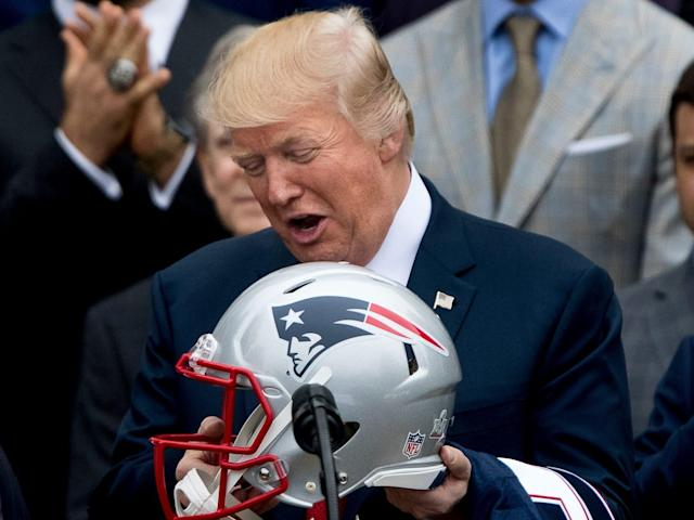 President Donald Trump is presented with a New England Patriots football helmet by Patriots head coach Bill Belichick and New England Patriots owner Robert Kraft during a ceremony on the South Lawn of the White House in Washington, Wednesday, April 19, 2017, where the president honored the Super Bowl Champion New England Patriots for their Super Bowl LI victory.