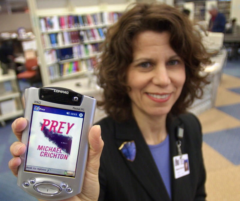 "FILE-- In a Jan. 7, 2003 file photo Sari Feldman, deputy director of the Cleveland Public Library, holds a PDA containing Michael Crichton's  book ""Prey,"" at the downtown Cleveland branch, Tuesday, Jan. 7, 2003.   E-book readers have been relatively slow to borrow digital works from the library, frustrated by a limited selection and by not even knowing if their local branch offers e-releases, according to a new study published Friday June 22, 2012.  (AP Photo/Mark Duncan, file)"