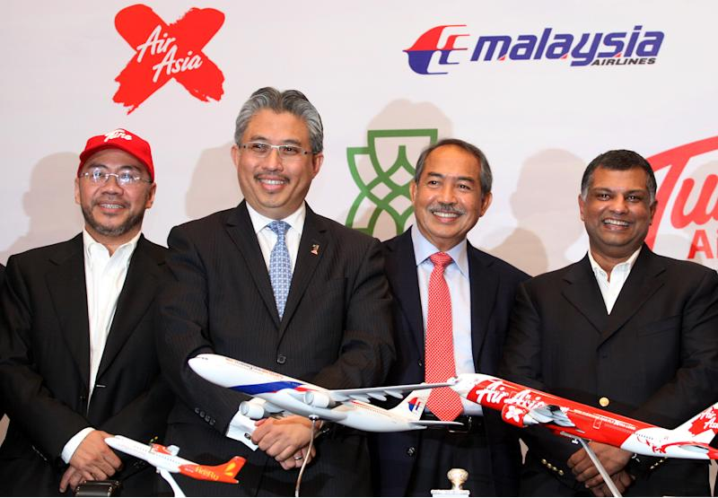 From right, AirAsia Chief Executive Tony Fernandes, Malaysia Airlines Chairman Md Nor Yusof, Khazanah Nasional managing director Azman Mokhtar, and Tune Group founder Kamarudin Meranun, pose together after a signing ceremony in Kuala Lumpur, Malaysia, Tuesday, Aug. 9, 2011.Budget carrier AirAsia and state-owned Malaysia Airlines formed an alliance Tuesday under a share swap deal to end their long rivalry and boost business.  (AP Photo/Lai Seng Sin)