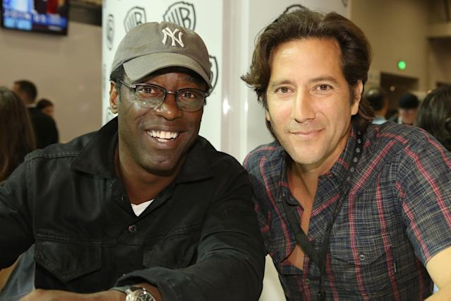 "Isaiah Washington and Henry Ian Cusick, from The CW's upcoming ""The 100,"" smile for fans at the Warner Bros. booth during the 2013 San Diego Comic-Con International held at the San Diego Convention Center on July 19, 2013 in San Diego, California."