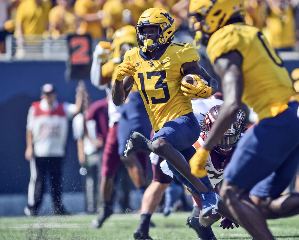 West Virginia wide receiver Sam James (13) picks up yards after a catch against Virginia Tech during the first half of an NCAA college football game in Morgantown, W.Va., Saturday, Sept. 18, 2021. (AP Photo/William Wotring)