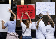 People in favor of a mask mandate for Cobb County schools hold signs against the window to the office during the school board meeting Thursday, Aug. 19, 2021, in Marietta, Ga. (Ben Gray/Atlanta Journal-Constitution via AP)