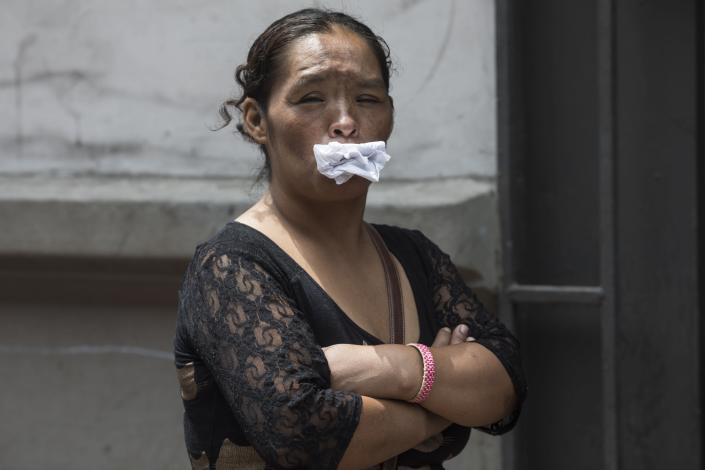 A woman holds paper in her mouth, her alternative to a face mask, as she waits in line for a free lunch from a charity that helps the homeless, amid the spread of the new coronavirus in Lima, Peru, Thursday, March 26, 2020. (AP Photo/Rodrigo Abd)
