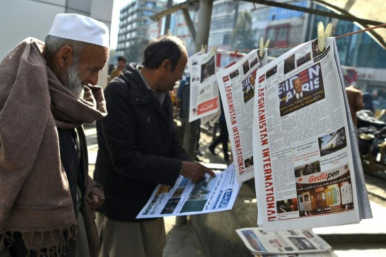 A man reads a local newspaper showing a photograph of newly elected US President Joe Biden, in Kabul on November 8, 2020, where some residents hope the President-elect may slow down the US withdrawal from Afghanistan