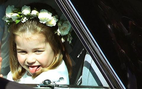 Princess Charlotte sticks out her tongue as she rides in a car to the wedding of Prince Harry and Ms Markle - Credit: Andrew Milligan/pool photo via AP