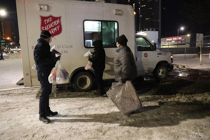 Jamie Winkler, Stephanie Taylor and Tracy Wolf take hot meals prepared on the Salvation Army's Bed and Bread truck to homeless people at Detroit's Hart Plaza on Feb. 5.