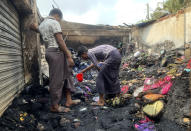 People inspect the debris after a fire in a makeshift market near a Rohingya refugee camp in Kutupalong, Bangladesh, Friday, April 2, 2021. The fire broke out early Friday when residents of the sprawling Kutupalong camp for Myanmar's Rohingya refugees were asleep. (AP Photo/Shafiqur Rahman)