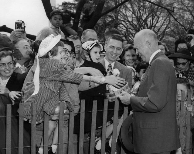 <p>President Dwight D. Eisenhower greets the crowd who have come for the Easter Egg Roll on the South Lawn of the White House in Washington, April 2, 1956. </p>