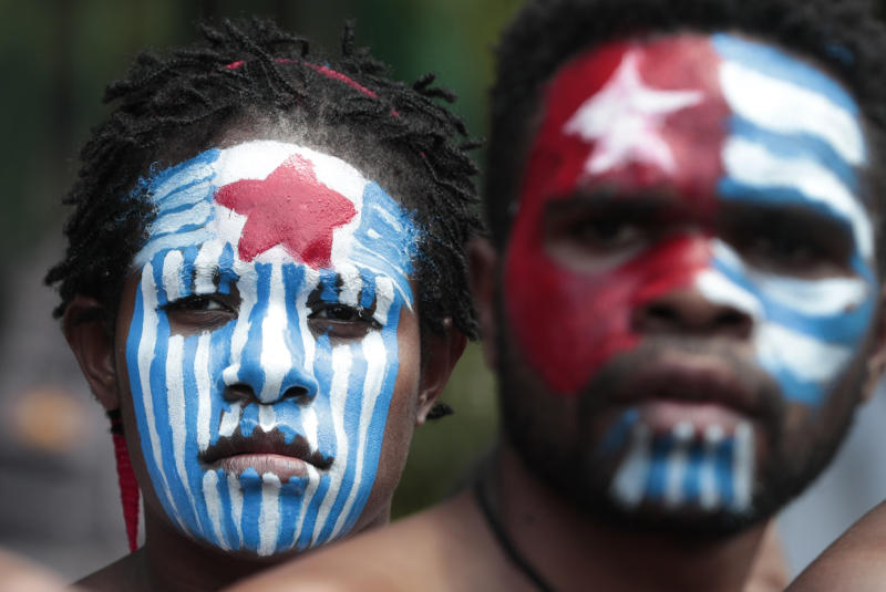 A Papuan activist with their face painted with the colors of the separatist Morning Star flag attend a rally near the presidential palace in Jakarta, Indonesia, Thursday, Aug. 22, 2019. A group of West Papuan students in Indonesia's capital staged the protest against racism and called for independence for their region. (AP Photo/Dita Alangkara)