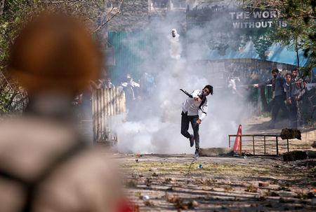 A Kashmiri student throws back a tear-gas canister fired by Indian police during a protest in Srinagar