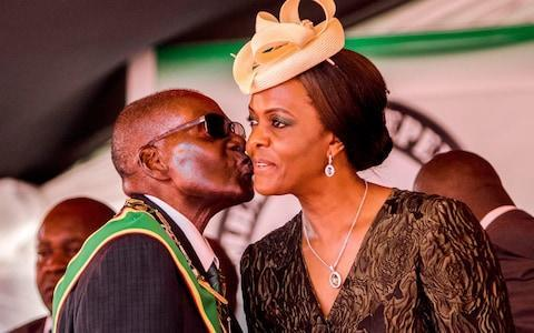 <span>Robert Mugabe kissing his wife and first lady Grace Mugabe during the country's 37th Independence Day celebrations </span> <span>Credit: Jekesai Njikizana/AP </span>