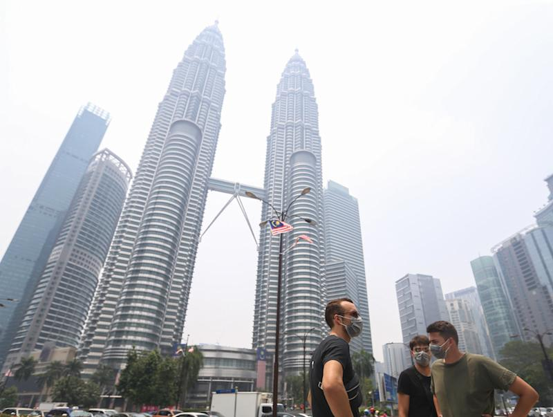 Tourists wear masks as they walk past the Petronas Twin Towers shrouded in haze in Kuala Lumpur September 12, 2019. — Picture by Firdaus Latif