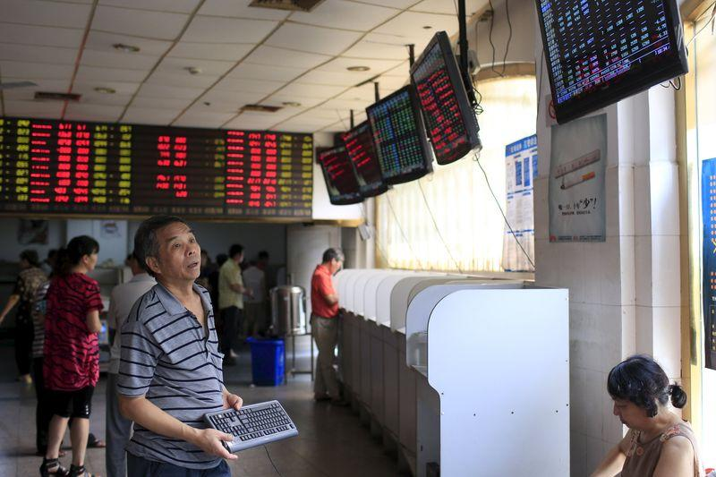 An investor looks at electronic boards showing stock information at a brokerage house in Shanghai