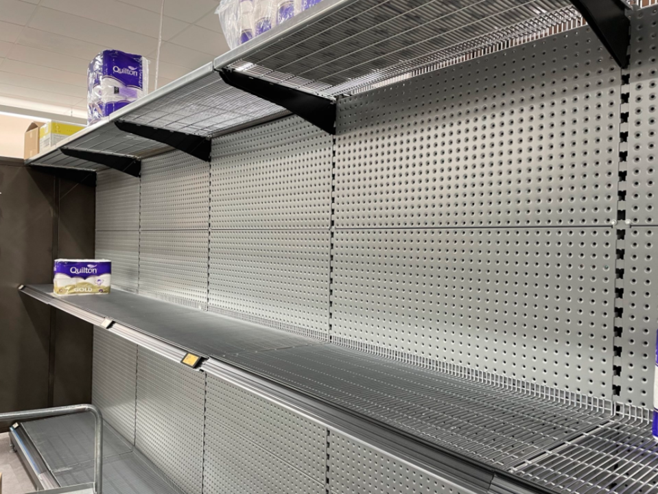 Empty shelves with just two packs of toilet paper left are seen at a Coles supermarket on the Northern Beaches.