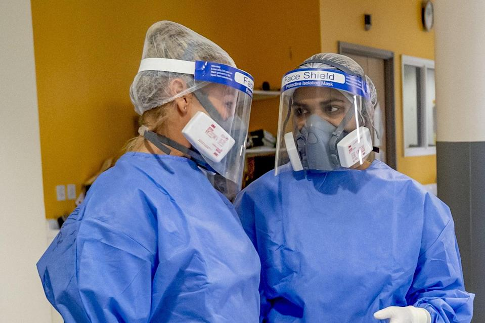 <p>Health workers wearing full personal protective equipment (PPE) on the intensive care unit (ICU) at Whiston Hospital</p> (PA)