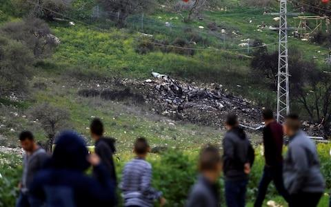 Bystanders look at the remains of an F-16 Israeli war plane near the village of Harduf, Israel  - Credit: Reuters