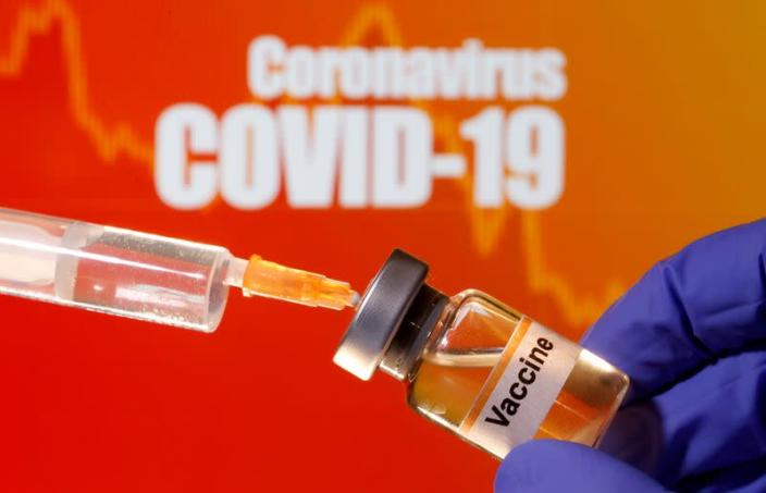 """FILE PHOTO: A small bottle labeled with a """"Vaccine"""" sticker is held near a medical syringe in front of displayed """"Coronavirus COVID-19"""" words in this illustration"""