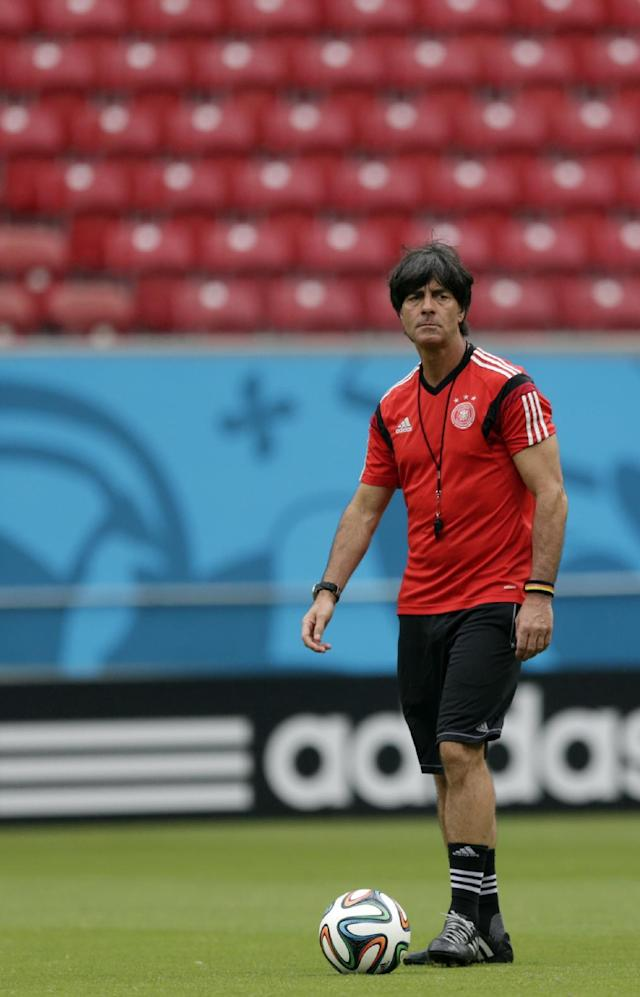 Germany's head coach Joachim Loew walks the pitch with a ball during a training session in Recife, Brazil, Wednesday, June 25, 2014. Germany will play the United States in group G of the 2014 soccer World Cup on June 26. (AP Photo/Julio Cortez)