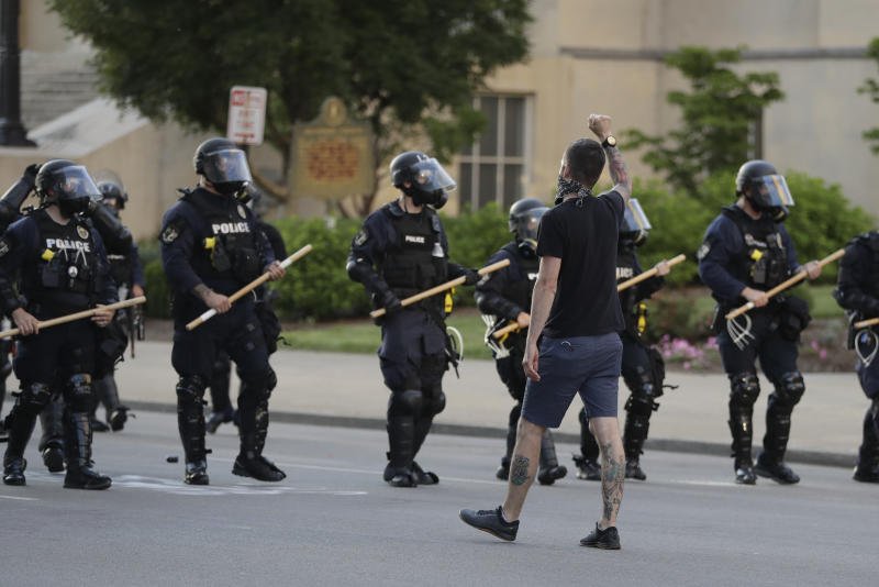 A protester walks with police officers during a protest over the deaths of George Floyd and Breonna Taylor, Saturday, May 30, 2020, in Louisville, Ky. Breonna Taylor, a black woman, was fatally shot by police in her home in March. (AP Photo/Darron Cummings)