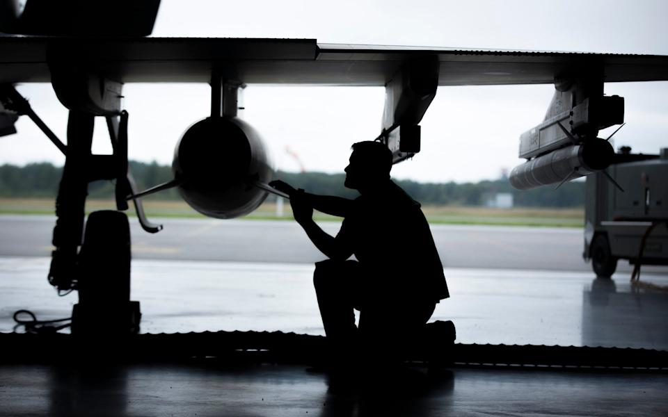 n engineer adjusts a radar guided air to air missile on a Typhoon jet