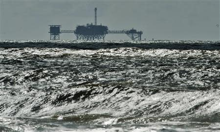An oil and gas drilling platform stands offshore as waves churned from Tropical Storm Karen come ashore in Dauphin Island, Alabama, October 5, 2013. REUTERS/Steve Nesius