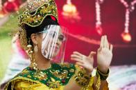 A dancer from Malaysia's pavilion performs wearing a face shield due to the coronavirus at Expo 2020, in Dubai, United Arab Emirates, Sunday, Oct. 3, 2021. (AP Photo/Jon Gambrell)