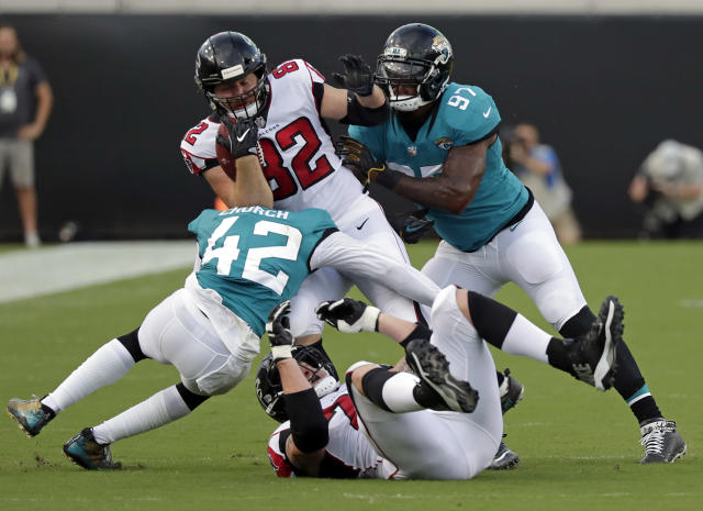 In this Aug. 25, 2018, photo, Jacksonville Jaguars defensive back Barry Church (42) and defensive tackle Malik Jackson (97) upend Atlanta Falcons tight end Logan Paulsen (82) after a reception during the first half of an NFL preseason football game in Jacksonville, Fla. The Jaguars relied on stout defense to win the AFC South and reach the conference title game last season. They return 12 of their top 14 players on that side of the ball and believe they will be even better this fall. (AP Photo/John Raoux)