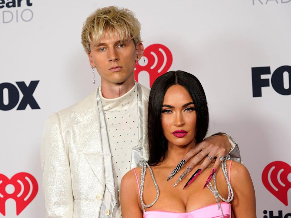 Machine Gun Kelly with his left arm around Megan Fox's shoulder at the red carpet of the iHeartRadio Music Awards.2021
