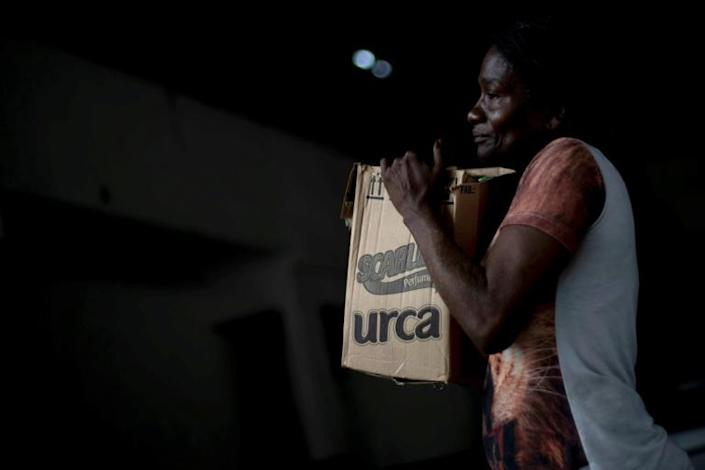 A Brazilian woman carries a box of food provided by an NGO in one of the favelas in Rio de Janeiro, in April 2020 (AFP Photo/MAURO PIMENTEL)