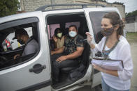 Miriam, 2nd left, and Luis Eduardo, 2nd right, listen to notary public Alessandra Lapoente during their drive-thru wedding at the registry office in the neighborhood of Santa Cruz, Rio de Janeiro, Brazil, Thursday, May 28, 2020. On Thursday alone, 15 couples were married at the drive-thru. (AP Photo/Silvia Izquierdo)