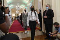 Seattle Storm's Jewell Loyd, center, followed by Breanna Stewart, walk into the East Room of the White House in Washington, Monday, Aug. 23, 2021, for an event with President Joe Biden to celebrate their 2020 WNBA Championship. (AP Photo/Susan Walsh)