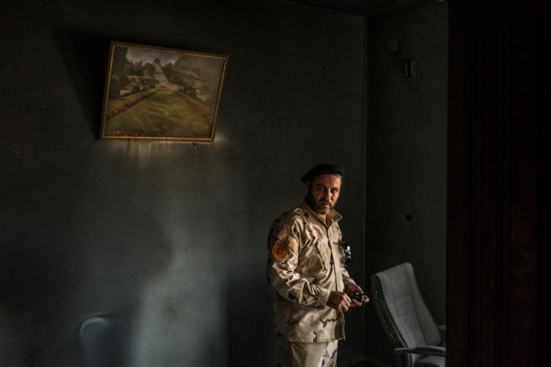 A fighter loyal to the GNA inside a building partially burned during a fight on the Yarmouk front line in Tripoli on July 1, 2019.   Emanuele Satolli