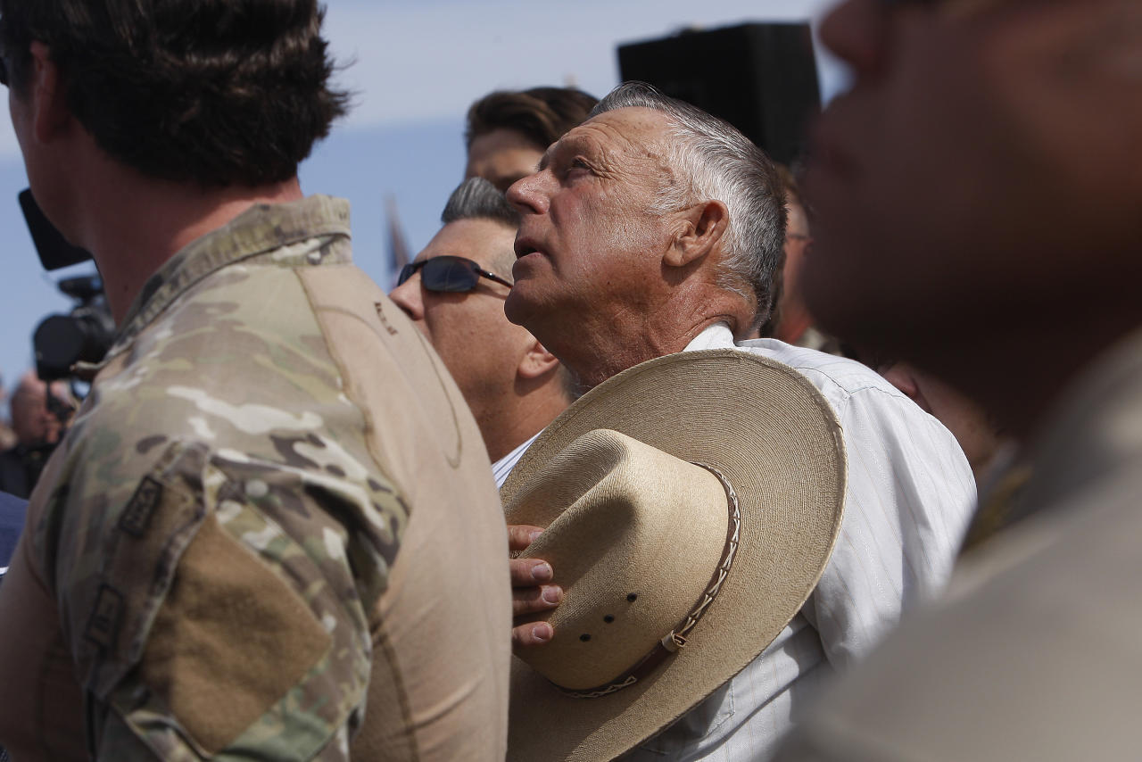 Surrounded by security personnel, rancher Cliven Bundy, middle, sings the National Anthem outside of Bunkerville while gathering with his supporters to challenge the BLM on April 12, 2014. (Jason Bean/Las Vegas Review-Journal)