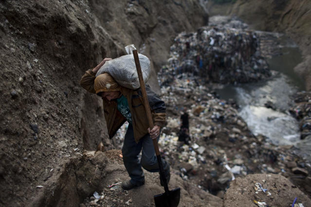 "<p>In this photo taken on Wednesday Oct. 5, 2011, a man who gave only his first name, Wilmer, carries a sack of metal he collected after working the entire day at the bottom of one of the biggest trash dumps in the city, known as ""the Mine,"" in Guatemala City. (Photo: Rodrigo Abd/AP) </p>"