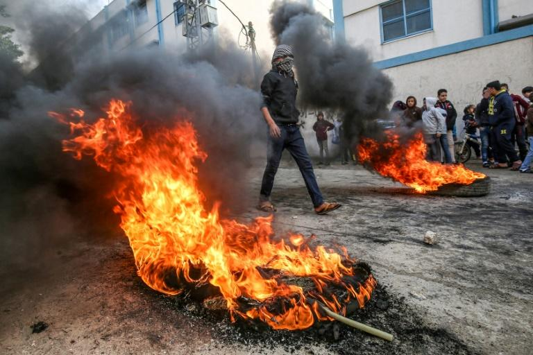 A Palestinian protester walks among burning tyres during demonstrations against a US-brokered Mideast peace plan in Khan Yunis in the southern Gaza Strip (AFP Photo/SAID KHATIB)