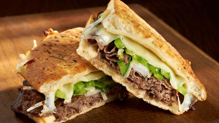 Philadelphia Cheesesteak Flatbread or Panini sandwich made with steak, provolone cheese and saute onions and bell peppers.