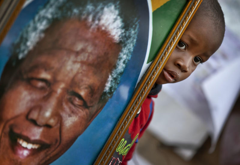 A young boy poses for a photograph of him holding a portrait of Nelson Mandela next to a wall of get-well messages and flowers laid outside the Mediclinic Heart Hospital where former South African President Nelson Mandela is being treated in Pretoria, South Africa Monday, July 8, 2013. There was no official update Monday morning on the health of the 94-year-old former president and anti-apartheid leader, who was admitted June 8 to the hospital for a recurring lung infection. (AP Photo/Ben Curtis)