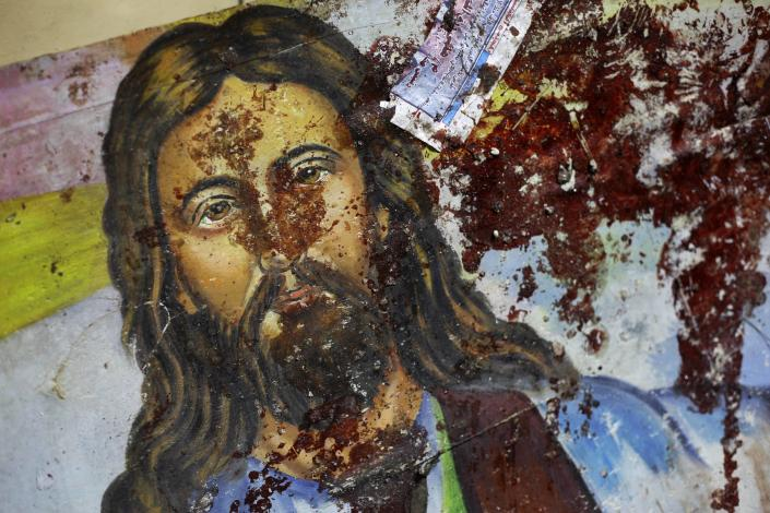 FILE - In this Saturday, Jan. 1, 2011 file photo, a blood-spattered poster of Jesus Christ is seen inside the the Coptic Christian Saints Church in the Mediterranean port city of Alexandria, Egypt, which killed some 21 people. Despite his rhetoric and promises to uphold the civil nature of Egypt, Shafiq seemed to some Egyptians an odd choice for Christians who suffered attacks under Mubarak's near 30 year-rule, culminating in the bombing of a church in Alexandria that killed 21 people attending a New Year's Even Mass more than a year ago. (AP Photo/Ben Curtis, File)