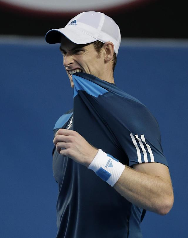 Andy Murray of Britain bites on his shirt during his fourth round match against Stephane Robert of France at the Australian Open tennis championship in Melbourne, Australia, Monday, Jan. 20, 2014.(AP Photo/Rick Rycroft)