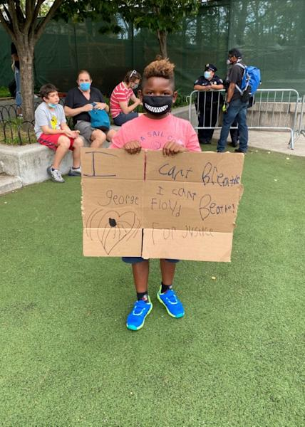Ellis holds a sign he made as he attends a memorial in Brooklyn's Cadman Plaza Park for George Floyd