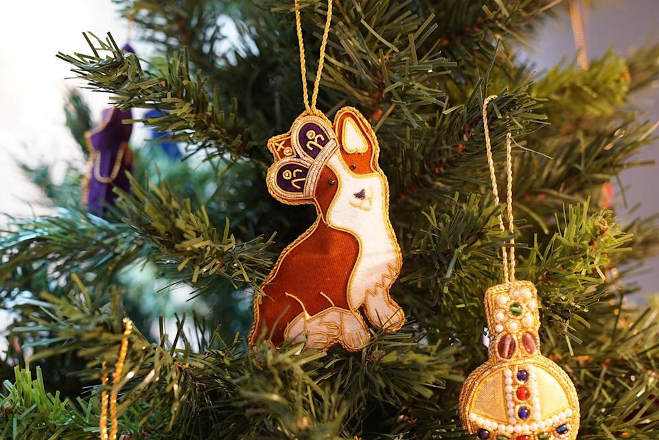 """<p>Decorate your Christmas tree with this sweet corgi hanging decoration. Corgis have been the pup of choice for the Queen since she was a teenager and this handmade decoration made from silk threads on a satin background will bring the royal touch to any tree.</p> <p><strong>Buy it! Historic Royal Palaces, Corgi with crown tree decoration, $14.60; <a href=""""https://www.historicroyalpalaces.com/corgi-with-crown-tree-decoration-1.html"""" rel=""""nofollow noopener"""" target=""""_blank"""" data-ylk=""""slk:historicroyalpalaces.com"""" class=""""link rapid-noclick-resp"""">historicroyalpalaces.com</a></strong></p>"""