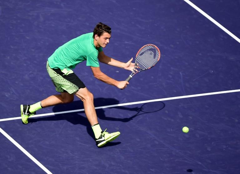 Taylor Fritz hits a backhand volley in his straight set victory over Benoit Paire of France at Indian Wells Tennis Garden