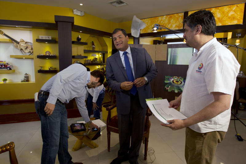 "Ecuador's President Rafael Correa, center, jokes as he prepares before an interview with The Associated Press in Portoviejo, Ecuador, Sunday, June 30, 2013. Correa said he had no idea Snowden's intended destination was Ecuador when he fled Hong Kong for Russia last week. He said the Ecuadorean consul in London committed ""a serious error"" without consulting any officials in the capital, Quito, when the consul issued a letter of safe passage for Snowden. At left AP reporter Michael Weinssenstein, at right Gonzalo Solano. (AP Photo/Martin Mejia)"