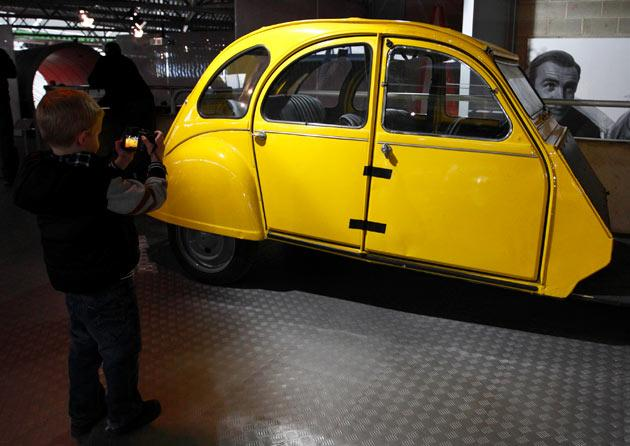 "A boy takes a photograph of a Citroen 2CV, which is believed to be the only 1 of 6 remaining from the filming of the 1981 Bond film ""For Your Eyes Only"" on display at the opening of a press preview of the Bond in Motion exhibition at the Beaulieu National Motor Museum at Brockenhurst in the southern English county of Hampshire on January 15, 2012. The Bond in Motion exhbition features fifty original iconic vehicles used in the James Bond films to celebrate fifty years of 007 and will open to the public from January 17. AFP PHOTO/ JUSTIN TALLIS"